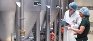 Zwei Mitarbeiter der Mischfabrik prüfen die Maschinenanforderungen der Kunden vor den Mischkesseln